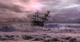 Sailing old ship in storm sea against dramatic sunset