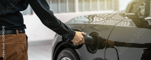 Foto  Banner of Closeup asian Technician hand is charging the electric car or EV in se