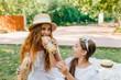 Excited girl with dark long hair looking how your mother eat bread during picnic. Hungry woman funny posing with sandwiches while her daughter laughing.