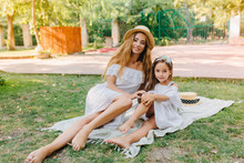 Barefooted Long-haired Girl Relaxing On Blanket With Little Sister And Sunbathing In Sunny Day. Outdoor Portrait Of Smiling Young Woman Chilling On The Grass With Cute Daughter In Elegant Dress.