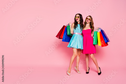 Fototapeta Full length body size close up photo two people beautiful she her ladies mall store carry many packs friendly mood wear sun specs colorful dresses formal-wear isolated pink bright background obraz na płótnie