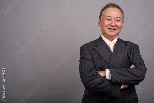 Fototapeta Portrait of mature Asian businessman against gray background obraz na płótnie