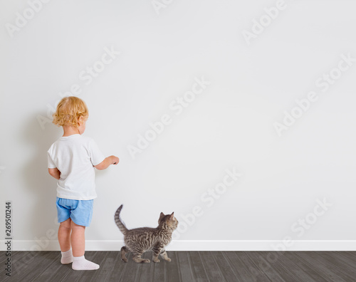 Fotografija  Baby boy drawing on wallpaper standing back to camera with little cat