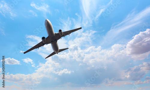 Papiers peints Avion à Moteur White passenger airplane in the clouds - Travel by air transport M