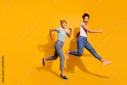 Full length body size view photo cheerful playful youth free time weekend holiday summer active race hurry childish curly haircut stylish trendy t-shirt jeans clothing isolated yellow background