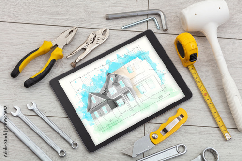 Photo sur Toile Kiev Tablet with construction tools and house plan concept