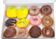Top View Flat Lay Of One Dozen Various Plain And Fancy Donuts In A White Box Isolated. Are Donuts Becoming A New Fad Or The New Trend. Gourmet Style Fancy Donuts.