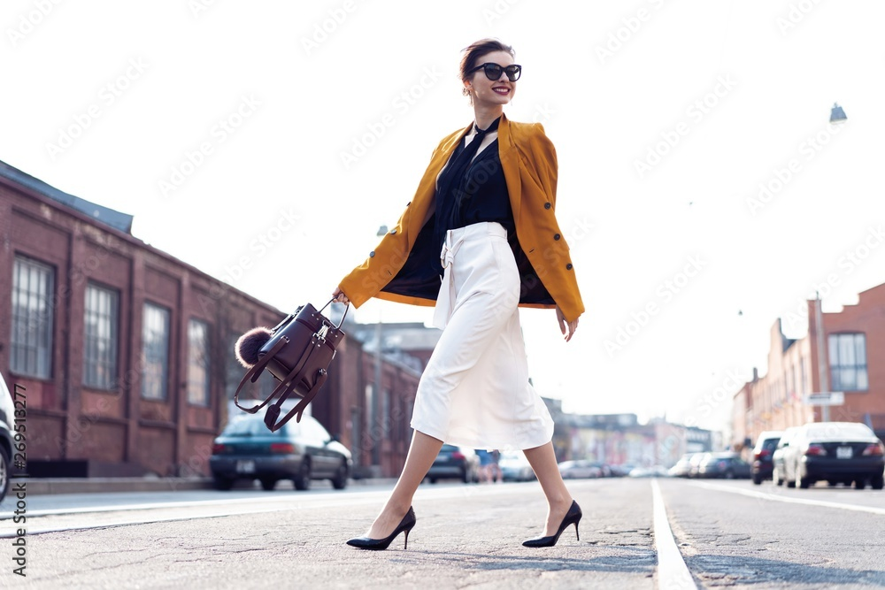 Fototapety, obrazy: Happy young business woman walking on the street.