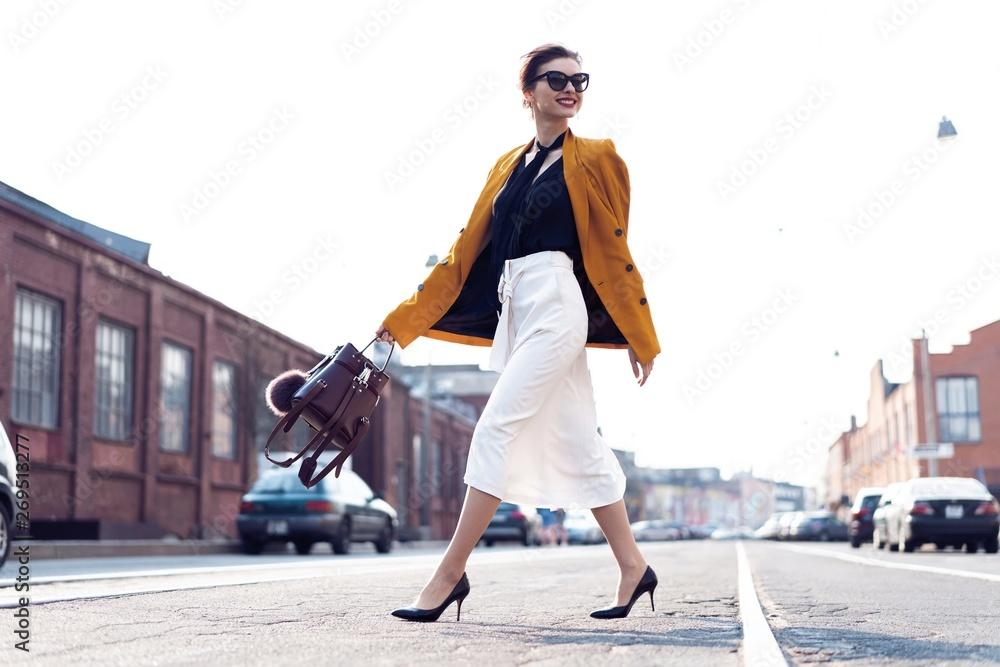 Fototapeta Happy young business woman walking on the street.