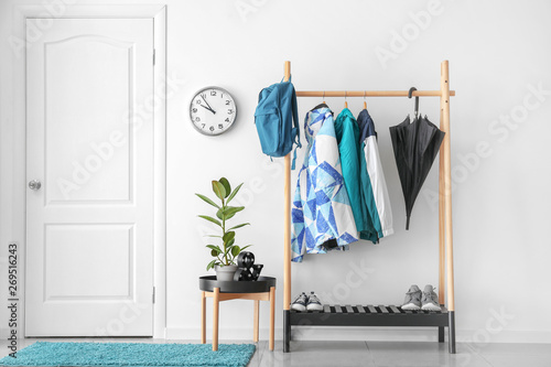 Obraz Rack with clothes in stylish interior of hall - fototapety do salonu