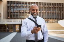 Happy Formal Businessman Using Phone On Street
