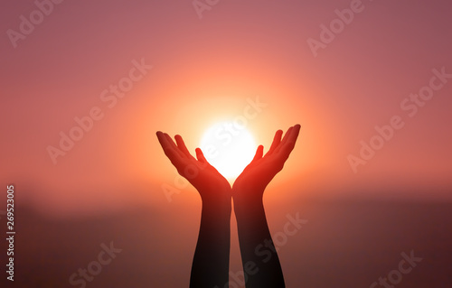 Fotomural  Free concept: Raised hands catching sun on sunset sky