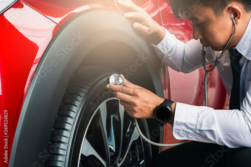 Foto  Asian man holding stethoscope with inspection car rubber tires