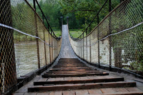 A beautiful,long wooden swinging bridge over a mountain river with wire railings