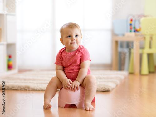 Fotografiet  Little smiling baby girl sitting on a pot