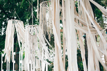 Stylish Boho Decor On Trees. Modern Bohemian Decoration Of White Macrame And Ribbons, Hanging On Branches In Summer Park. Wedding Decor And Arrangement. Stylish Arch For Ceremony