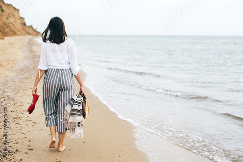 Foto  Stylish hipster girl walking barefoot on beach, holding bag and shoes in hand
