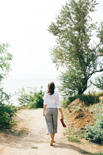 Stylish Hipster Girl Relaxing On Beach.  Happy Young Boho Woman In White Shirt Walking Barefoot On Tropical Island At Sandy Cliff And Trees. Summer Vacation. Space For Text