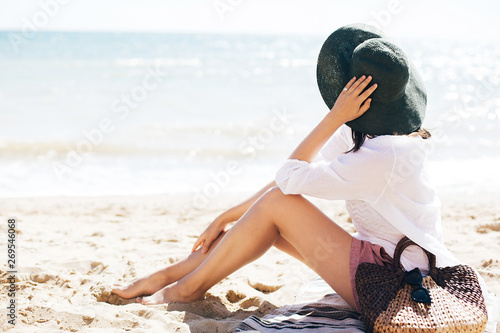 Stylish hipster girl in hat sitting on beach with straw bag and tanning near sea waves Wallpaper Mural