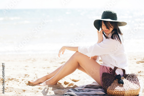 Obraz Stylish hipster girl in hat sitting on beach and tanning near sea waves. Summer vacation. Happy boho woman relaxing and enjoying sunny warm day at ocean. Space for text - fototapety do salonu