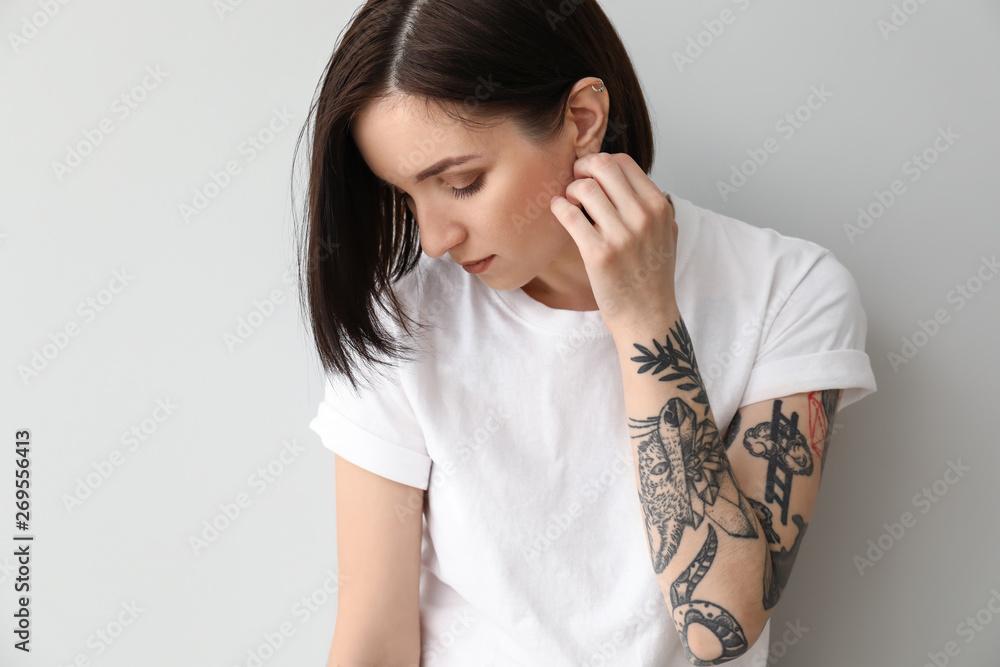 Fototapeta Stylish tattooed woman on light background