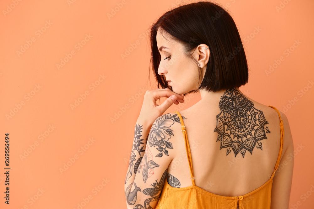 Fototapeta Beautiful tattooed woman on color background