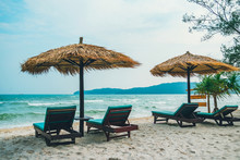 Beach Calm Scene With Sunbeds And Straw Umbrellas Under Coconut Palms Close To Caribbean Sea. Tropical Paradise With Chaise Lounges On White Sand,