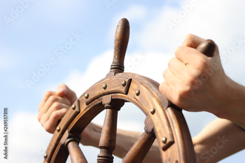 Steering hand wheel ship on sky background, hand hold hand wheel фототапет