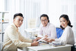 Portrait of young Asian business people working at the table in team and looking at camera during meeting at office