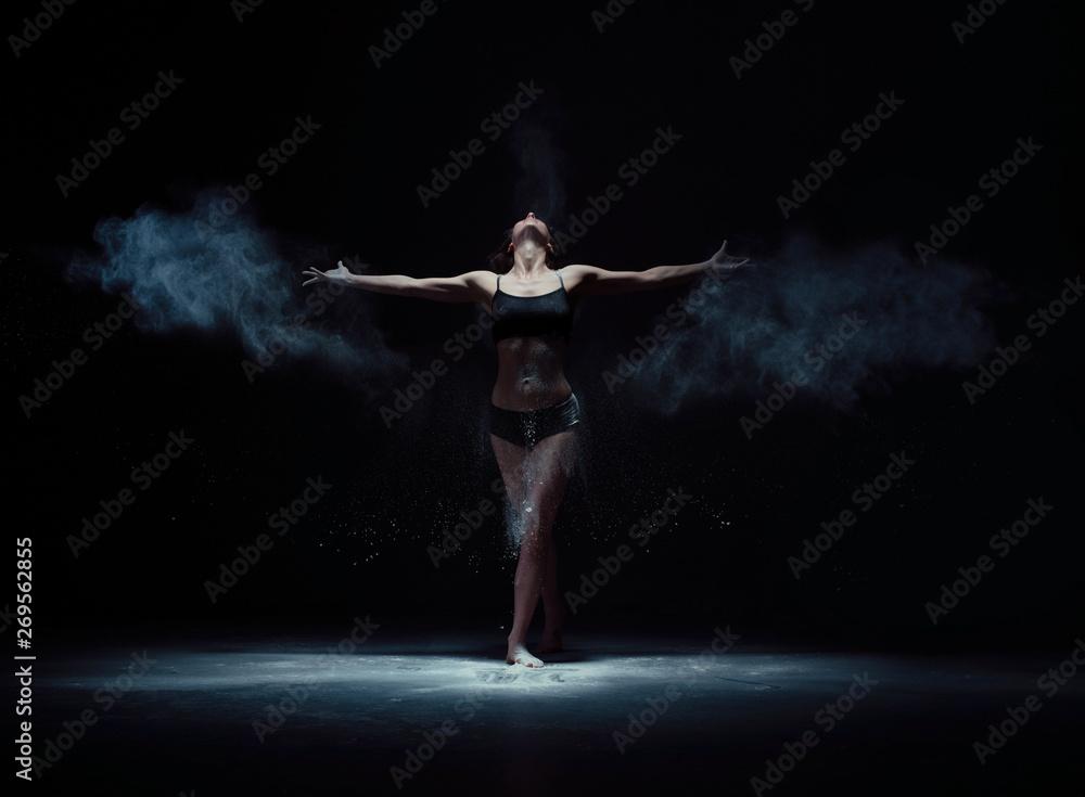 Fototapeta Graceful woman dancing in white dust cloud shot