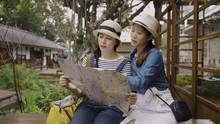 Two Happy Young Elegant Girl Friends Tourists Sitting On Bench Holding Paper Map Checking Route Plan. Women Travelers Relax On Chair Outside Japanese Style Wooden House Discussing Next Destination.