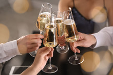 Friends Clinking Glasses Of Champagne In Restaurant, Closeup