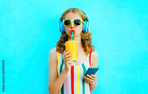 La pose en embrasure Magasin de musique Portrait cool girl drinking fruit juice holding phone listening to music in wireless headphones on colorful blue background