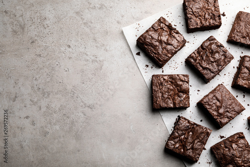 Flat lay composition with fresh brownies and space for text on gray background. Delicious chocolate pie