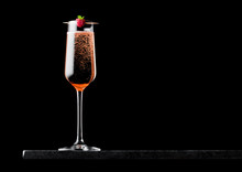 Elegant Glass Of Pink Rose Champagne With Raspberry On Stick On Black Marble Board On Black Background. Space For Text