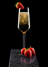 Elegant Glass Of Yellow Champagne With Strawberry On Top And Fresh Berries On Black Marble Board On Black Background.