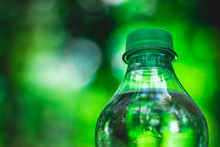 Plastic Bottle Top Full With Water With Green Cap In A Park Or Garden With Green Trees In Blurred Background – Recyclable Beverage Container That Protects The Nature