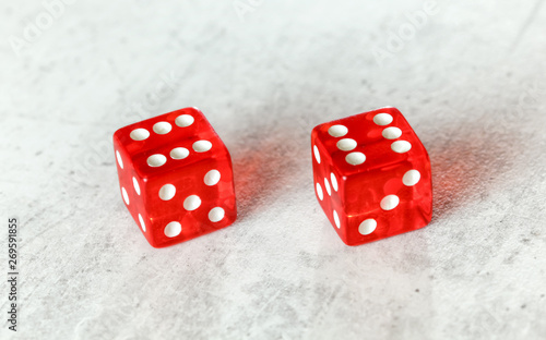 Photo  Two translucent red craps dices on white board showing Boxcars or Midnight (doub