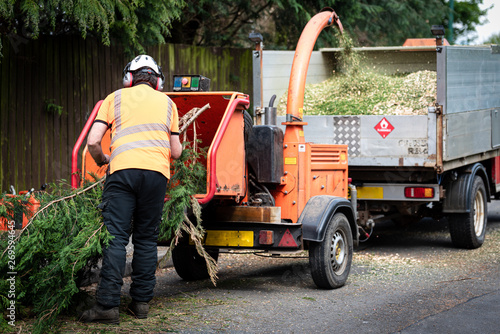 Photo Male Arborist using a working wood chipper machine