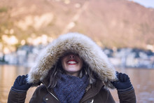Cheerful Woman In Winter Clothes Covering Eyes With A Hood