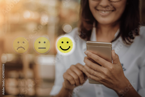 Fotografía Businesswoman pressing face emoticon on virtual touch screen at smartphone