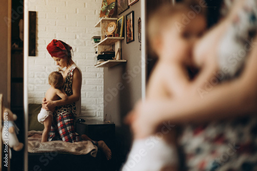 Fotografía  weekdays young mother who feeds her daughter feeding in their bedroom photos from the reflection in the mirror