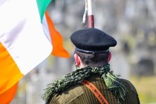 A Man In Paramilitary Uniform, With An Irish Tricolour As He Commemorates The Easter Rising Of 1916