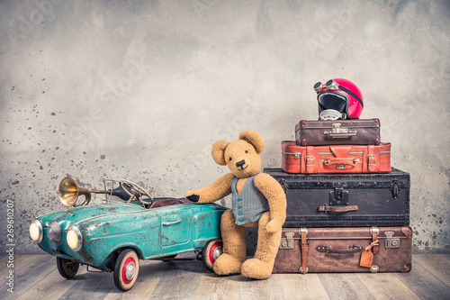 Obraz Teddy Bear toy standing near rusty retro  pedal car from 60s, antique travel trunks luggage, old leather valises, red helmet with outdated goggles front loft background. Vintage style filtered photo - fototapety do salonu