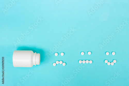 Fotografía Funny faces made of pills and a plastic bottle on a blue background