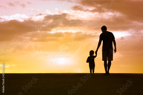 Fotografering Silhouette of loving father walking side by side with son holding hands