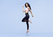 Woman in trendy sportswear jumping. Smiling beautiful slim brunette young girl in fashion leggings and pink top expressing happy emotions on blue background.