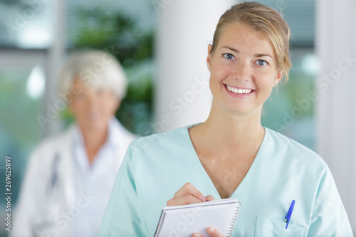 woman nurse in white coat records in a notebook - 269625897
