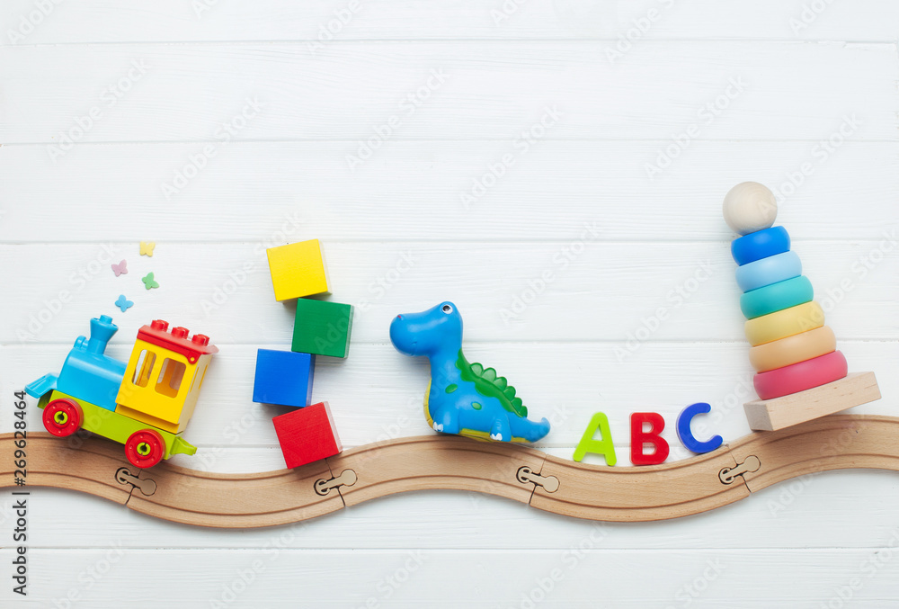 Fototapety, obrazy: Kids toys on toy wooden railway on white wooden background with copy space