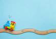 canvas print picture - Kids toy train on toy wooden railway on blue background with copy space